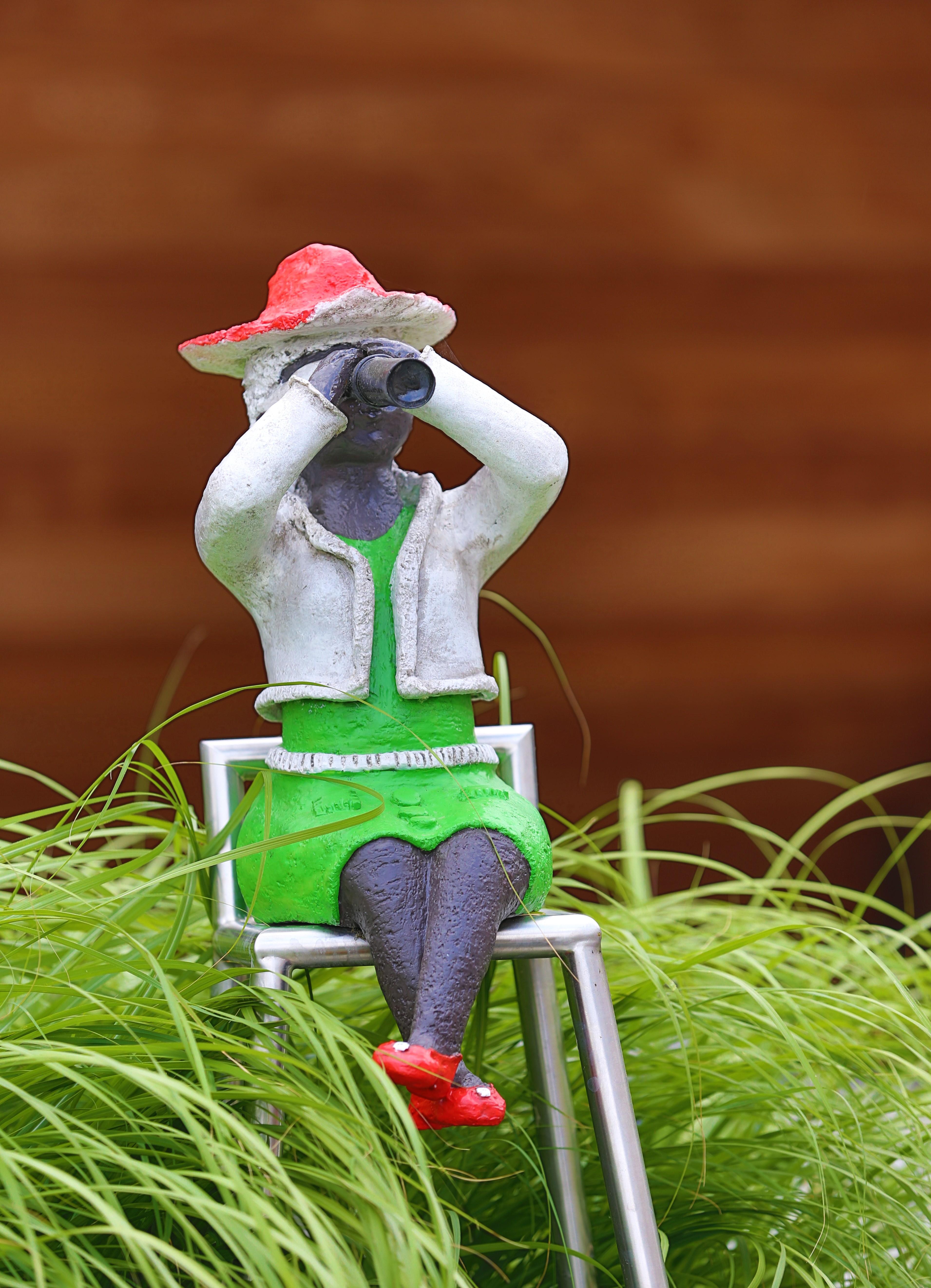 Dikke madam in herfstoutfit met verrekijker Kunst voor buiten